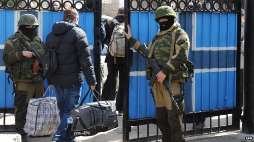 Ukrainian military officials leave their posts, escorted by Russian forces